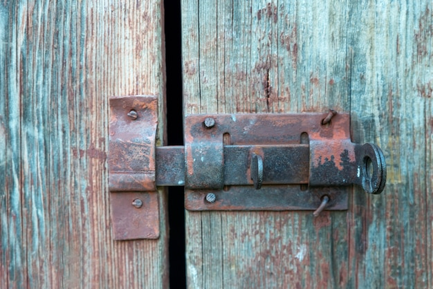 Altes eisen, rostiger riegel am alten holztor. verschlossene tür.