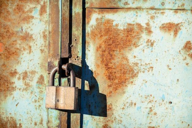 Altes eisenscheunenschloss auf einer rostigen metalltür