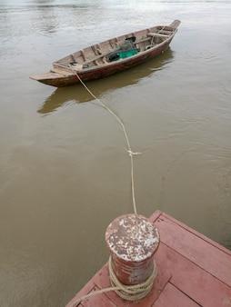 Altes fischen, das auf das ruhige wasser bei mae klong river schwimmt