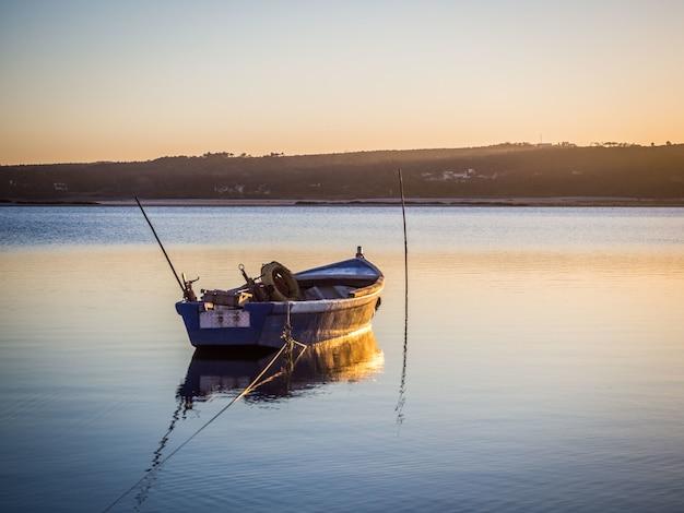 Altes fischerboot am fluss mit dem atemberaubenden blick auf den sonnenuntergang