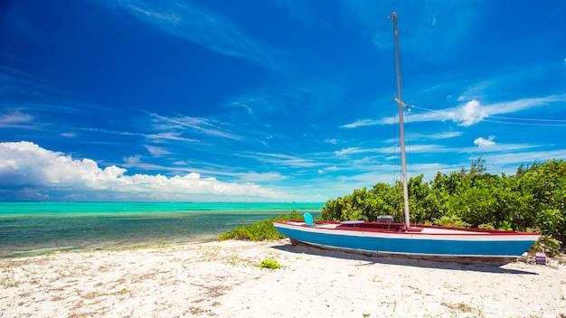 Altes fischerboot auf einem tropischen strand in den karibischen meeren