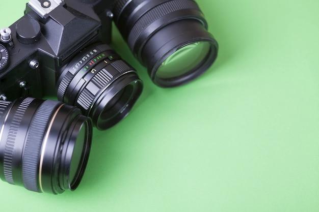 Altes fotoalbum, fotos, kamera, zarte rosa blumen auf einem dunklen hölzernen hintergrund.