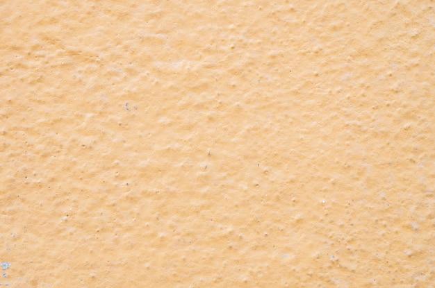 Altes gelb der nahaufnahme gemalter zementwandhintergrund