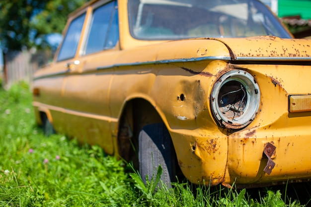 Altes gelbes autowrack im vintage-stil. verlassenes rostiges gelbes auto. nahaufnahme der scheinwerfer der vorderansicht eines rostigen, kaputten, verlassenen autos in der nähe des hauses. konzept des verlassenen gebrauchtwagens.