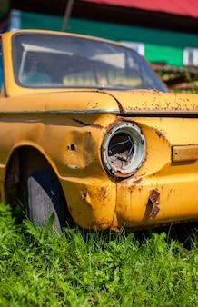 Altes gelbes autowrack im vintage-stil. verlassenes rostiges gelbes auto. nahaufnahme der scheinwerfer der vorderansicht eines rostigen, kaputten, verlassenen autos in der nähe des hauses. russland, gebiet kemerowo, 23. juli 2021