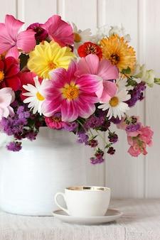 Altes geschirr, eine weiße tasse und eine untertasse auf dem tisch und gartenblumen. stillleben mit einem blumenstrauß.