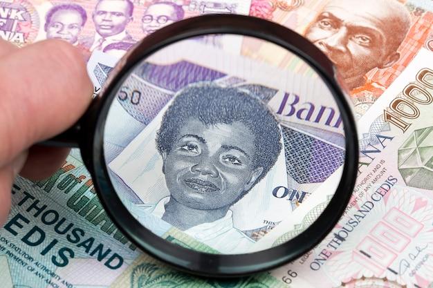 Altes ghanaisches geld in einer lupe ein geschäftshintergrund