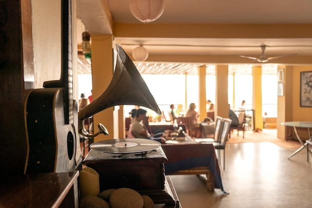 Altes grammophon, gitarre und leute im restaurant, fokus auf grammophon, nahaufnahme
