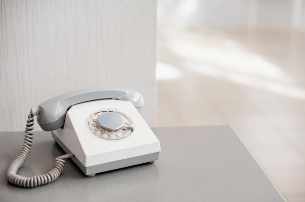 Altes graues telefon auf hellem hintergrund. seitenansicht