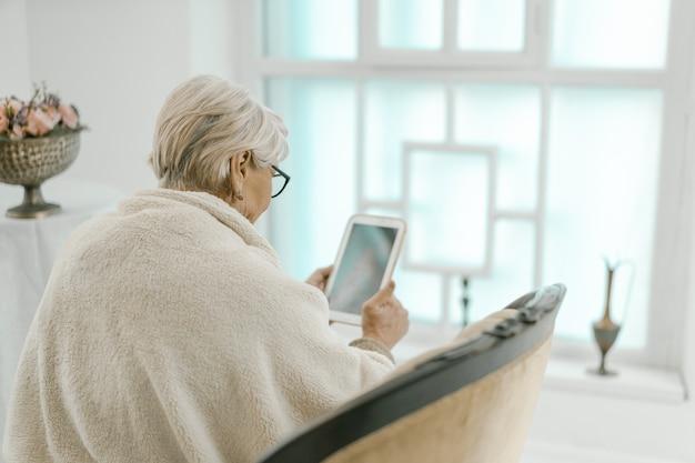 Altes grauhaariges weibliches entspannen zu hause mit einer tablette in ihrer hand.