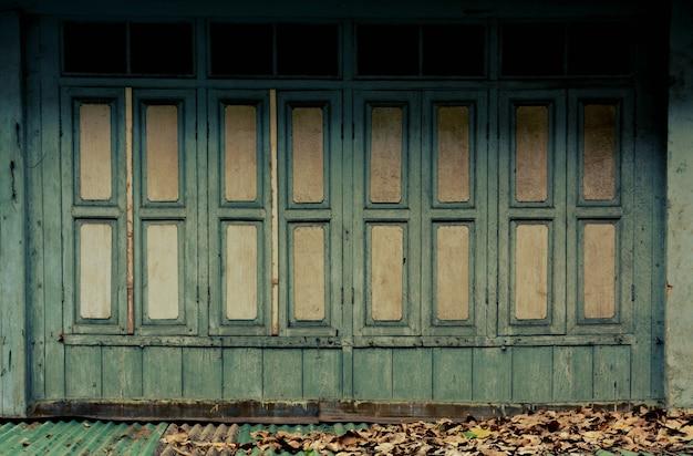Altes grünes hölzernes fenster am klassischen hölzernen gebäude - weinleseart