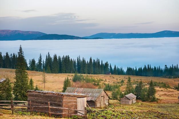 Altes haus vor der schönen natur mit wolkenozean, grasfeld und bergen