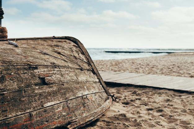 Altes hölzernes boot gedreht auf dem strand