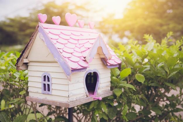 Altes hölzernes reizendes vogelhaus des vogelhauses im garten mit morgensonnenlichtweinlesefarbton