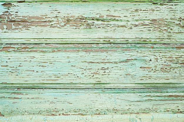 Altes holz mit rissen grün lackiert.