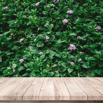 Altes holzbrett mit abstraktem natürlichem grünem blatthintergrund für produktpräsentation