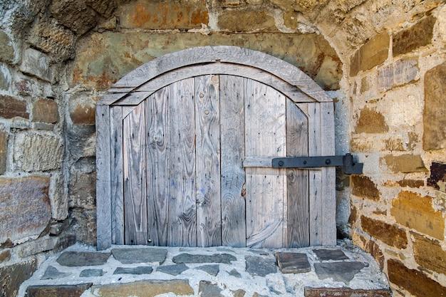Altes holzfenster der mittelalterlichen backsteinmauer