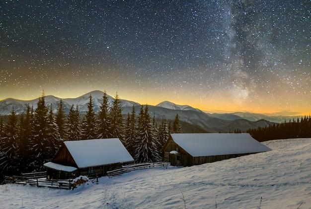 Altes holzhaus, hütte und scheune, brennholzhaufen im tiefschnee im bergtal, fichtenwald, bewaldete hügel am dunklen sternenhimmel und milchstraße-kopierraumhintergrund. bergwinternachtlandschaft.