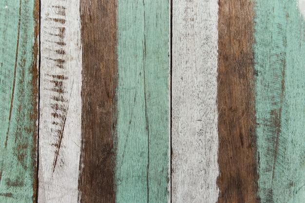 Altes holzmaterial der weinleseholzhintergrundbeschaffenheit. vintage tapetenfarben gemustert aus bunten paneelen verwitterter bemalter holzbretter