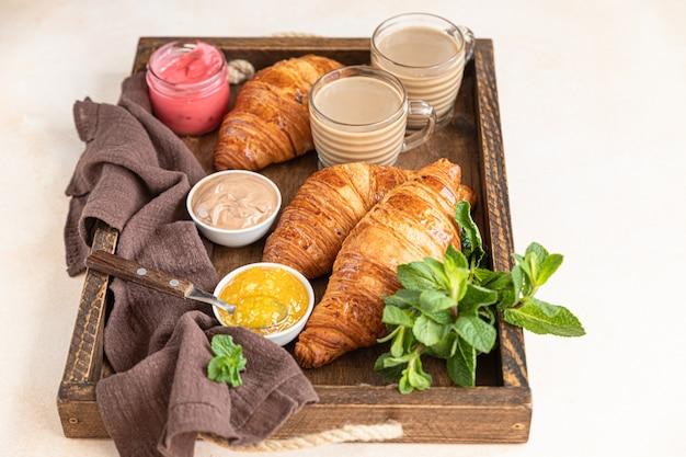 Altes holztablett mit knusprigen croissants, marmelade, schokoladencreme und kaffee