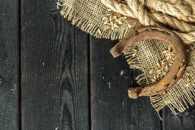 Altes hufeisen und seil auf hölzernen brettern