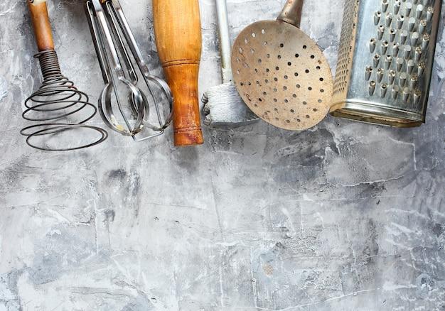 Altes küchenwerkzeug auf grauem beton. retro küche, vintage kochwerkzeugsatz. draufsicht.