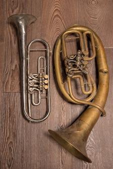 Altes messingblasinstrument und horn auf einem hölzernen hintergrund.