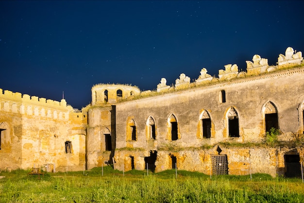 Altes mittelalterliches schloss nachts unter dunkelblauem himmel mit vielen sternen