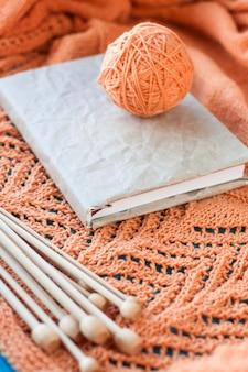 Altes notizbuch für die aufzeichnungen, garnball und stricknadeln, die auf hölzernem orange gestricktem plaid liegen