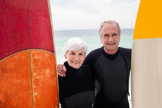 Altes paar mit surfbrett stehen am strand