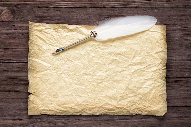 Altes papier auf brauner holzbeschaffenheit mit weißer feder
