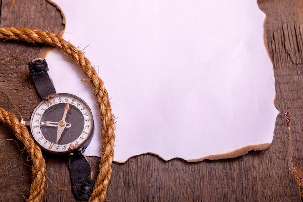 Altes papier mit kompass, messer und seil auf weinleseholztisch. draufsicht des leeren raumes für ihren text.