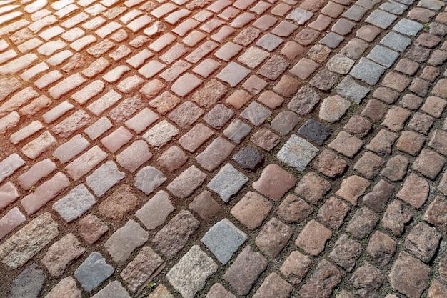 Altes pflastersteinmuster. beschaffenheit des alten deutschen kopfsteins in der stadt im stadtzentrum gelegen. kleine granitfliesen. antike graue bürgersteige.
