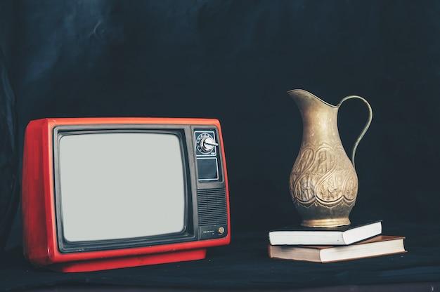 Altes retro- fernsehen, indem es blumenvasen auf bücher setzt