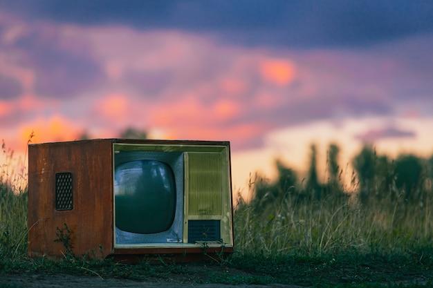 Altes retro-fernsehgerät auf einer feldstraße unter den strahlen der untergehenden sonne
