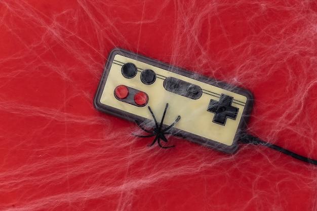 Altes retro-gamepad auf rot mit spinnweben und spinnen. halloween-thema. spinnenphobie