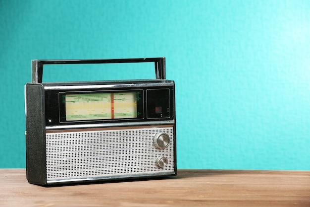 Altes retro-radio auf tabelle auf grünem wandhintergrund