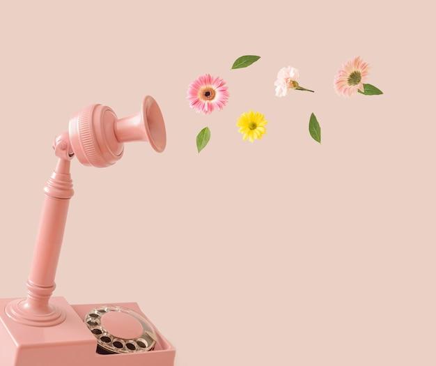 Altes retro-telefon und blumen, die in mehreren farben auf einem pastellrosa hintergrund fliegen