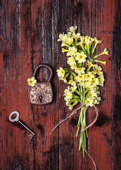 Altes rostiges vorhängeschloss mit frühlingsgelben schlüsselblumen und einem alten schlüssel auf einem rustikalen hölzernen hintergrund.