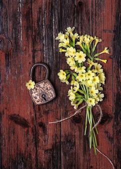 Altes rostiges vorhängeschloss mit wilden gelben schlüsselblumen des frühlinges auf einem rustikalen hölzernen hintergrund.