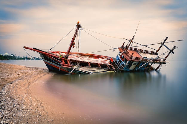 Altes schiffswrack auf dem strand während des sonnenuntergangs in pattaya, thailand