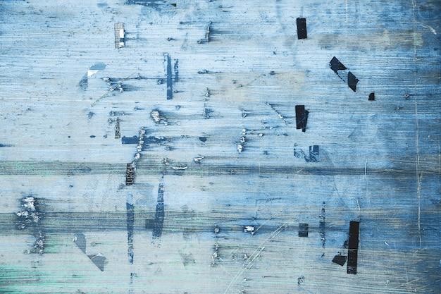 Altes schwarzes brett in blauer farbe. billboard mit zerrissenem, geschältem poster. sperrholzplatte mit abgenutzter werbebotschaft. grunge städtischen hintergrund, straßenbeschaffenheit im freien.