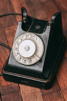 Altes schwarzes telefon auf dem boden, weinlese