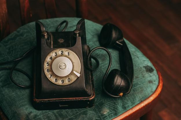 Altes schwarzes telefon auf einem stuhl