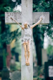 Altes steinkreuz mit figur des gekreuzigten jesus christus