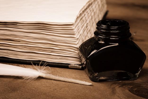 Altes tagebuch, ein tintenfass und eine feder