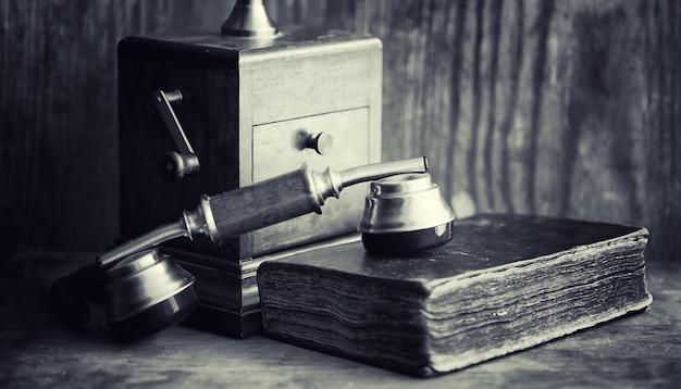 Altes telefon und retro-buch auf dem schreibtisch. das telefon der vergangenheit auf einer alten holzarbeitsplatte. ferngespräche des 19. jahrhunderts.