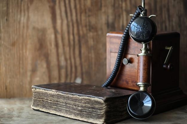 Altes telefon und retro-buch auf einem holztisch