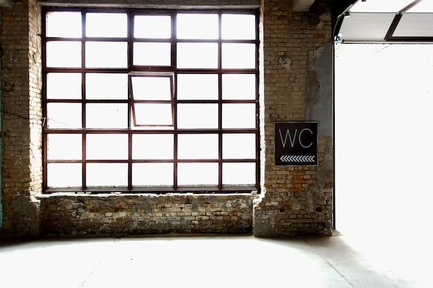 Altes toilettenschild, das an verlassener fabrik hängt
