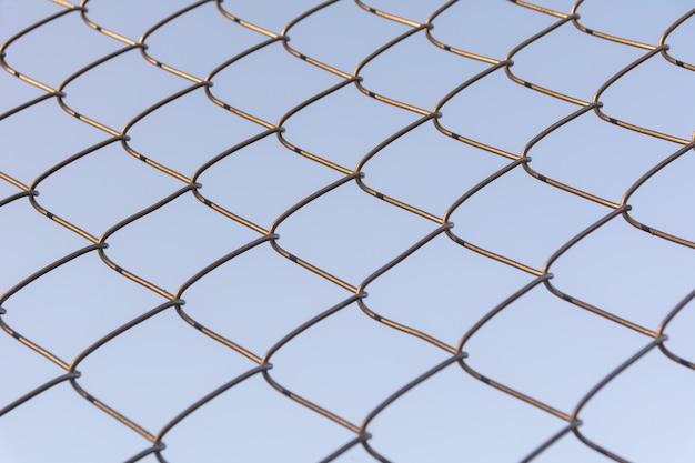Altes und rostiges eisennetz eingewickelt auf hintergrund des blauen himmels.